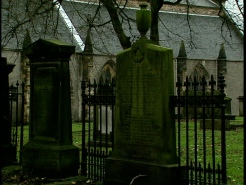 ms, tombs on greyfriars kirkyard, church in background edinburgh, scotland - placca di montaggio fissa video stock e b–roll