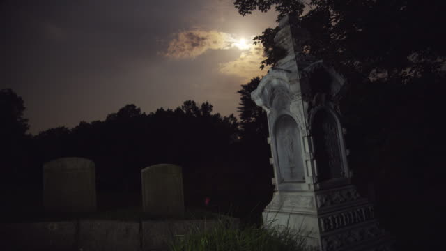 vidéos et rushes de tombstone at night with full moon - pierre tombale