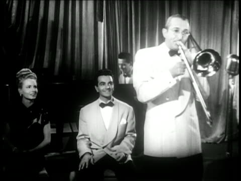 tommy dorsey playing trombone with seated man woman in background / feature film - trombone stock videos & royalty-free footage