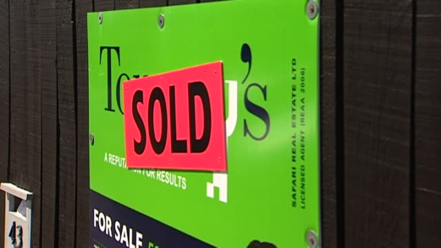 tommy's real estate auction sign with sold stickers on fence outside property - real estate sign stock videos & royalty-free footage