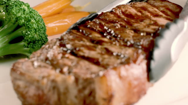 CU tong places cooked ribeye steak on white plate garnished with baby carrots