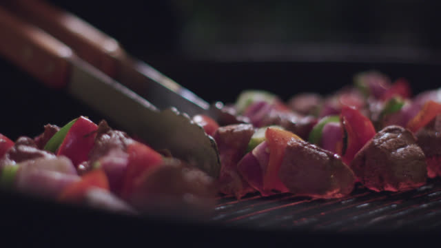 ECU SLO MO. Tongs flip steak kabobs with colorful peppers as they cook on smoking grill.