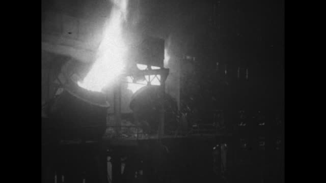 vídeos de stock, filmes e b-roll de tongs lift whitehot cylinder from vat flames burn workers place hoses / note exact month/day not known - metarlúgica