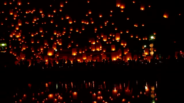 Tons of lanterns across dark sky.