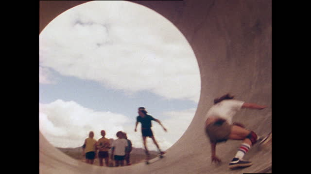 tony alva, a professional skateboarder, skateboards in a concrete pipe in the desert with another skateboarder before falling; 1978. - young men stock videos & royalty-free footage