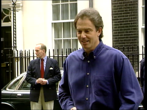 tony and cherie blair: baby leo born; england: london: downing street: ext policeman carrying flowers and a carrier bag across to door of number 10... - teddy boy stock videos & royalty-free footage