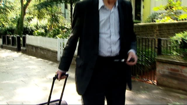 vídeos de stock, filmes e b-roll de tony benn invents new 'seat case' ext benn along with 'seat case' invention and benn sitting at bus stop on seat case benn sitting at bus stop on... - tony benn