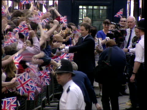 stockvideo's en b-roll-footage met tony blair and wife cherie greet crowds waving flags on day he became prime minister 02 may 97 - downing street