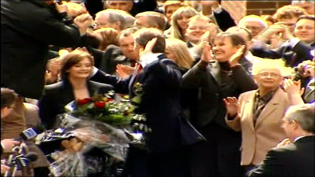 Blair speech Sedgefield EXT Blair and wife Cherie carrying a bouquet of roses along through supporters after leaving Labour Club