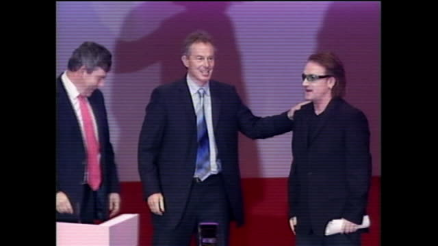 tony blair announces resignation: blair's britain; tx 29.9.2004 england: brighton: labour party conference: bono on stage with blair and gordon brown... - フリーズフレーム点の映像素材/bロール