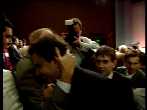 tony blair is hugged by neil kinnock amid media scrum as he leaves labour leadership election conference as new labour leader london 21 jul 94 - トニー ブレア点の映像素材/bロール