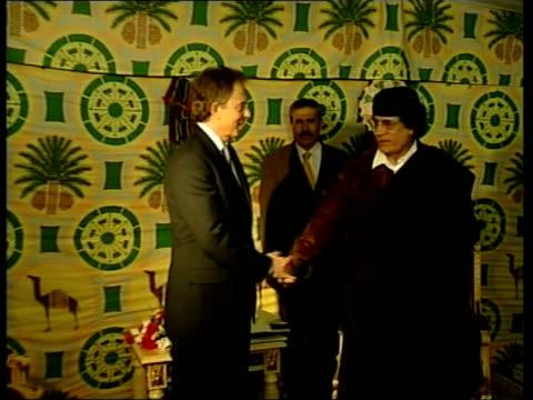 tony blair meets colonel gaddafi pool libya tripoli british prime minister tony blair from plane shakes hands with libyan prime minister receives... - muammar gaddafi stock videos & royalty-free footage