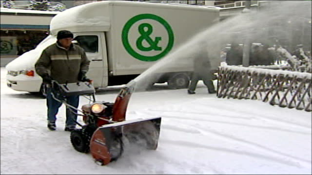 tony blair speech to world economic forum ext / snow man clearing snowy pavement with small snow plough - itv weekend evening news stock-videos und b-roll-filmmaterial