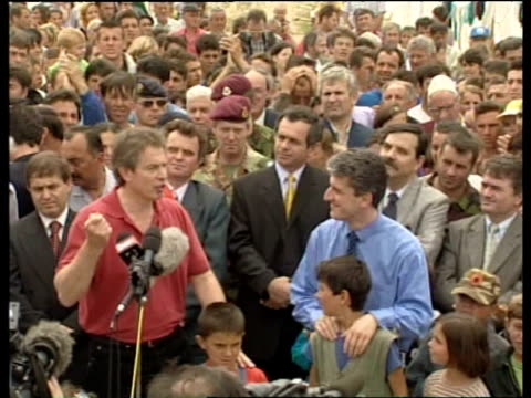 Tony Blair stands amidst large crowd of refugees promising to help