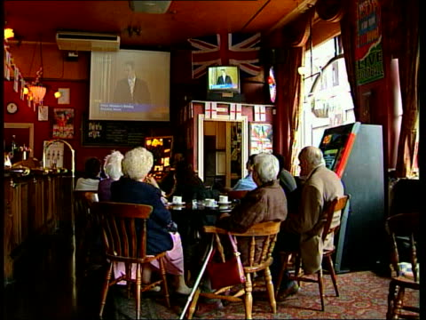 televised news conference; itn bv people watching tv in pub vox pops woman questioning why immigrants are allowed into the country - bericht film und fernsehen stock-videos und b-roll-filmmaterial