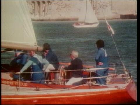 tony blair to take holiday in britain; lib isle of wight: edward heath sailing on yacht lib london: b&w harold wilson towards from train with dog as... - エドワード ヒース点の映像素材/bロール