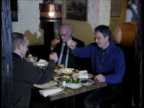 tony blair's visit to moscow; int blair sitting at table in bar with russian president vladimir putin as drinking vodka: tgv blair & putin sitting at... - ウォッカ点の映像素材/bロール