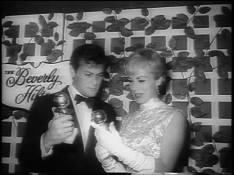 tony curtis + janet leigh holding golden globe awards + kissing / newsreel - ゴールデングローブ賞点の映像素材/bロール