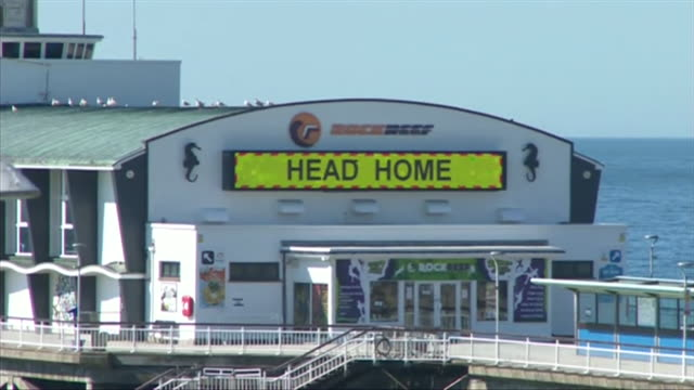 too busy head home message on bournemouth pier during coronavirus lockdown for people visiting the beach during coronavirus lockdown - bournemouth stock-videos und b-roll-filmmaterial
