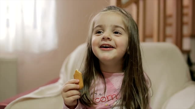 too cute 3 years girl smiling and eating cookies - biscuit stock videos and b-roll footage