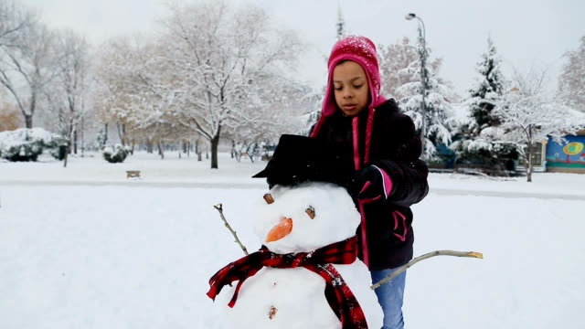 too cute african ethnicity girl makes a snowman,winter fun for kids - snowman stock videos & royalty-free footage
