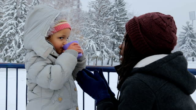 too cute little girl drinking tea on the snow,winter vacations concept - ethnicity stock videos & royalty-free footage