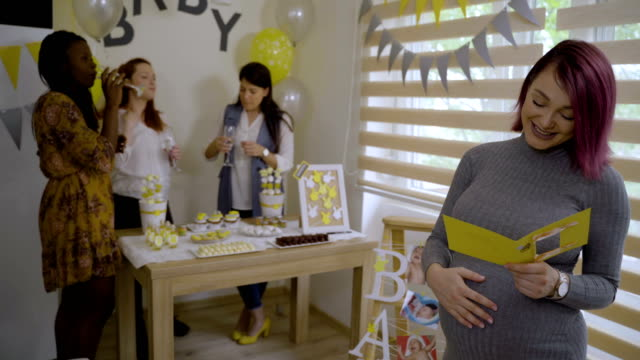 troppo carino giovane donna incinta leggendo biglietto di auguri e smile-baby evento doccia - baby shower video stock e b–roll