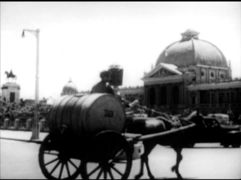 stockvideo's en b-roll-footage met tehran iran toopkhaneh square w/ large building pool camels cars on road traffic modern building busy maidan w/ traffic around fountain - 1951
