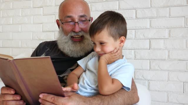 Toothy Lächeln Großvater mit seinem Enkel als sie etwas zusammen zu lesen