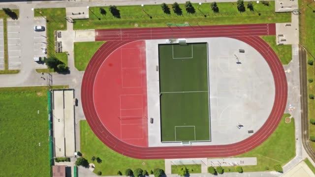 ランニングトラック、サッカー、バスケットボールを備えたスポーツアスレチックとレクリエーションセンターのトップ空中写真 - 球技場点の映像素材/bロール