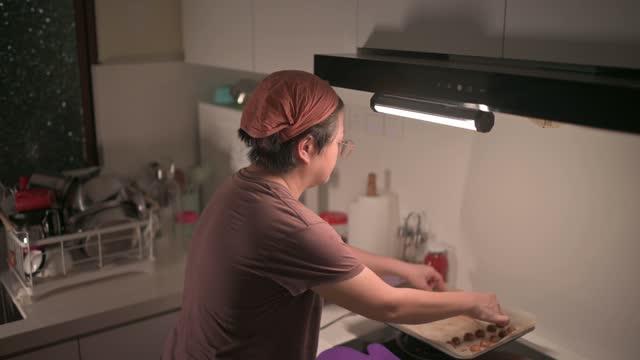 top-winkelansicht asiatische chinesische mittlere erwachsene frau, die zu hause in der küche gebackenen erdnusskeks aufhebt - einzelne frau über 30 stock-videos und b-roll-filmmaterial