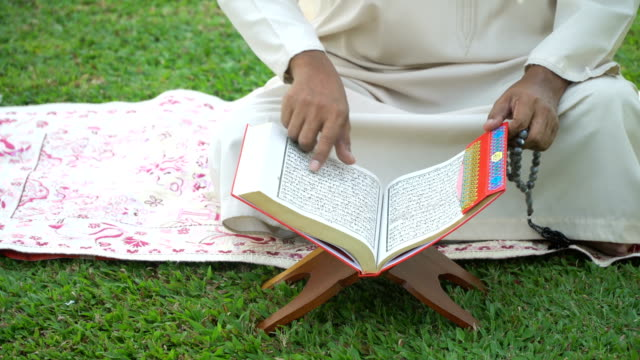 top angle view:  muslim grandfather read quran in public park - koran stock videos & royalty-free footage