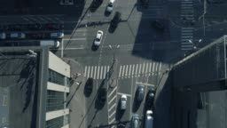 Top Down Aerial Drone Tracking Shot of a White Car Moving Through City Traffic at Daytime.
