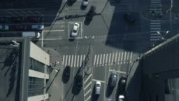 Top Down Aerial Drone Tracking Shot: White Autonomous Self Driving Car Moving Through City. Concept: Artificial Intelligence Scans Surrounding Environment, Detecting Cars, Avoids Traffic Jams.