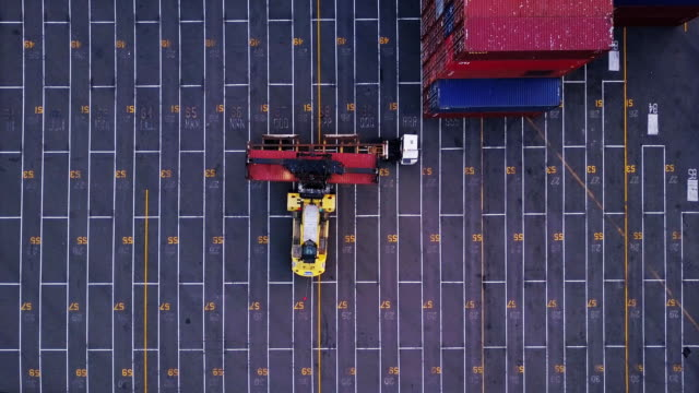 top down aerial shot of truck being loaded in container yard - lastzug stock-videos und b-roll-filmmaterial
