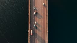 Top down aerial view of car traffic on bridge over river, drone shot