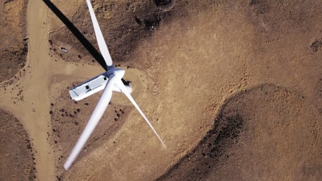 top down drone shot of arid hillside over wind turbine - wind turbine stock videos & royalty-free footage