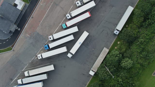top down drone shot of lorries parked at distribution centre - distribution warehouse stock videos & royalty-free footage