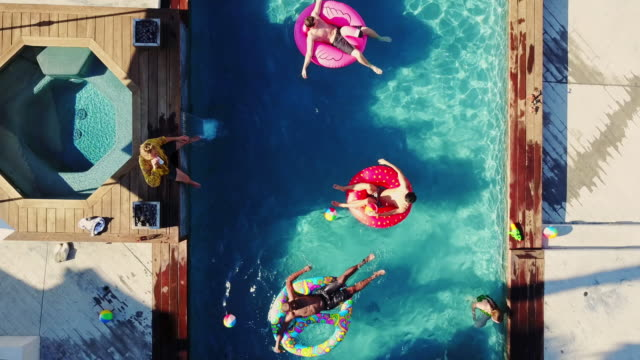 top down drone shot of people playing around in a backyard swimming pool - vacations stock videos & royalty-free footage