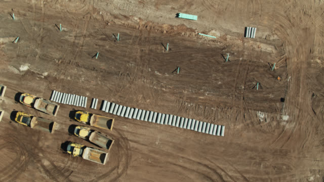 vídeos y material grabado en eventos de stock de top down drone shot of pipes and cables being laid in reclaimed land for suburban housing in florida - barrio con viviendas idénticas