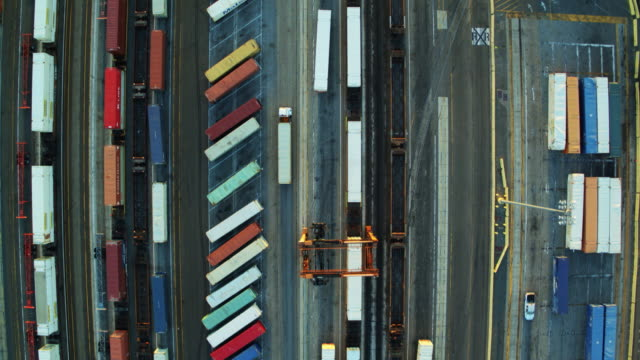top down drone shot of rows of shipping containers and truck trailers in vast shipping yard - heavy goods vehicle stock videos & royalty-free footage