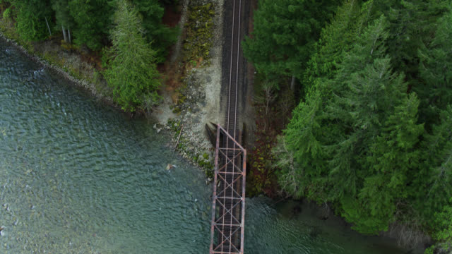 top down drone shot of rusty railroad bridge over skykomish river - railroad track stock videos & royalty-free footage
