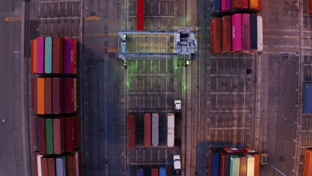 top down drone shot of straddle carrier changing position in container yard - straddle carrier stock videos & royalty-free footage