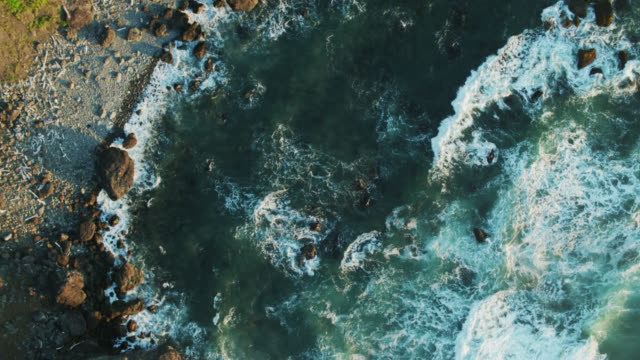 stockvideo's en b-roll-footage met top down drone shot of waves crashing on cliffs on the oregon coast - oregon coast