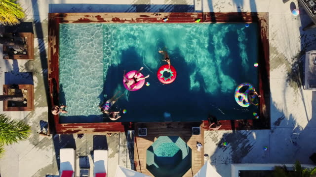 top down drone shot pulling up from people playing around in a backyard swimming pool - california stock videos & royalty-free footage