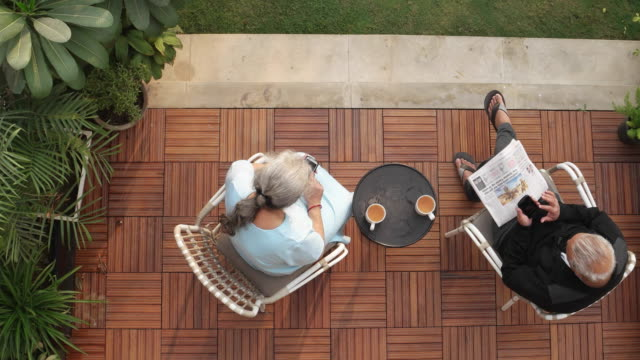 Top down of an elder couple having their morning drink in the backyard, while spending time on their mobile devices