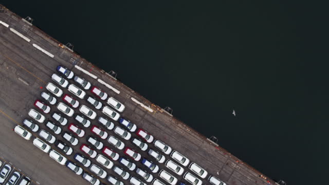 Top Down Rotating Drone Shot of Lot Filled With Cars on Dockside