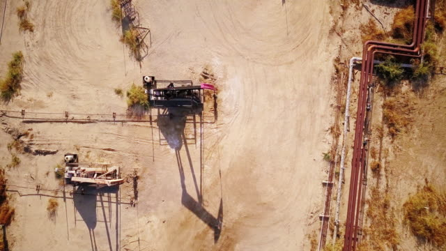 top down shot of nodding donkey oil field and curving pipeline - freshly painted stock videos & royalty-free footage
