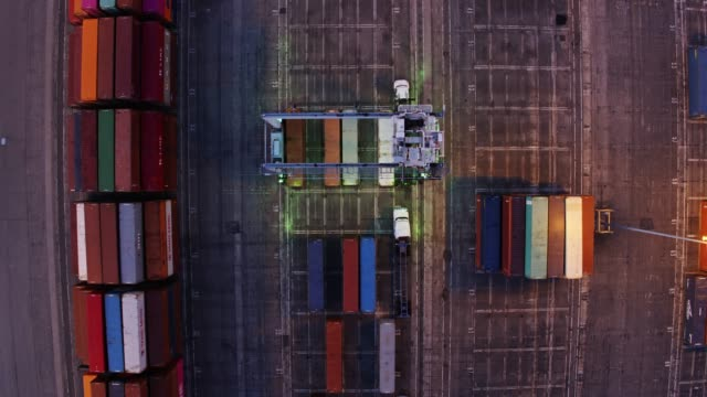 top down static drone shot of straddle carrier in container terminal yard - straddle carrier stock videos & royalty-free footage