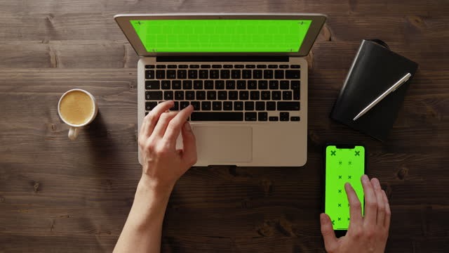 top down view of a work desk with green screen on laptop and smartphone - table top view stock videos & royalty-free footage